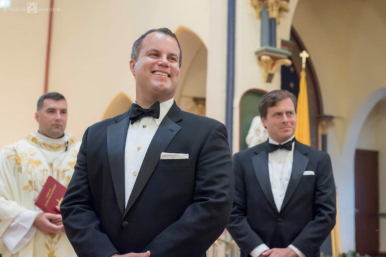 groom watching as his bride walks down the aisle on their wedding day