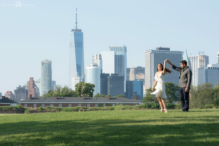 couple posing for their engagement photos at Governors Island with NYC skyline behind them