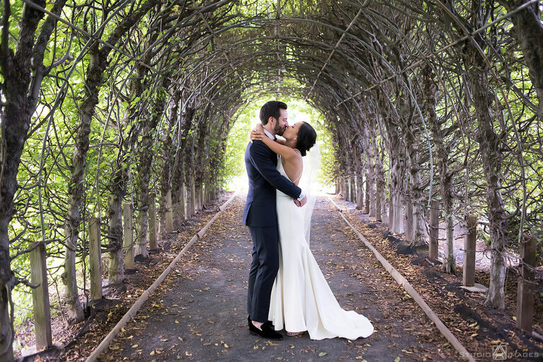 couple kisses in the allee at Celebrate at Snug Harbor on their wedding day