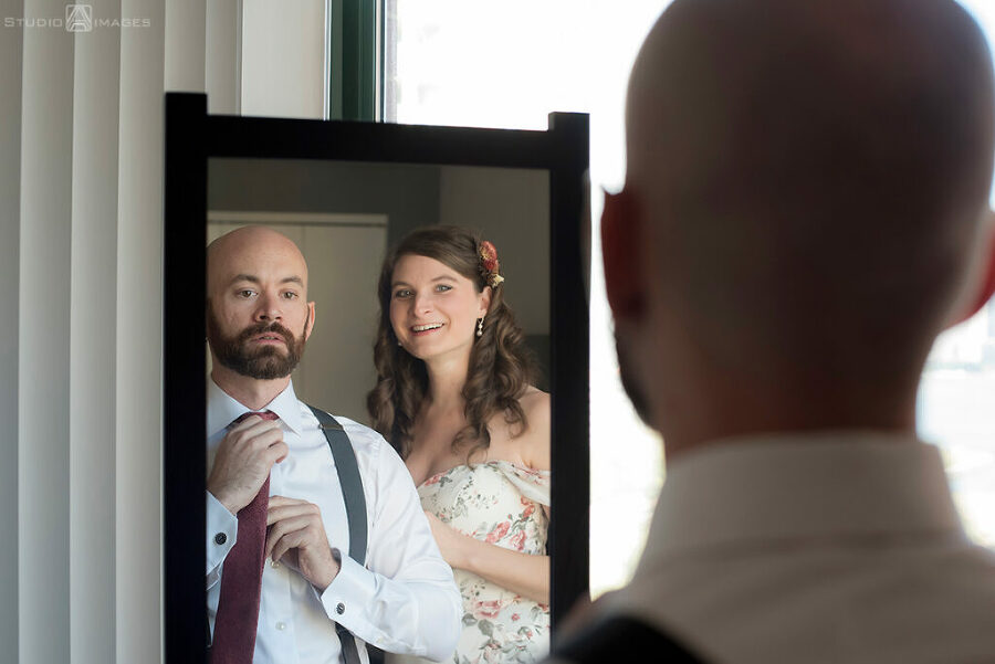 bride and groom getting ready for their wedding in their apt in Jersey City