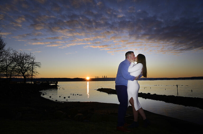 couple kissing against beautiful sunrise in Nyack during their engagement session