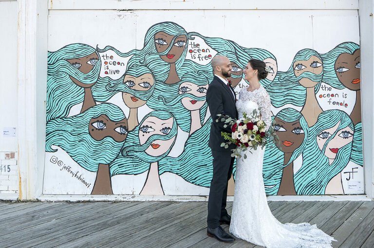 bride and groom in front of Asbury Park murals on their wedding day in Asbury Park.